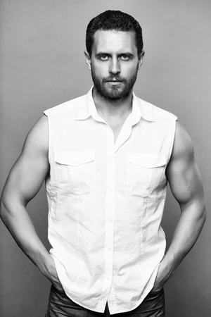灰色のスタジオの背景に白いシャツとジーンズのハンサムな筋肉ひげの男 写真素材
