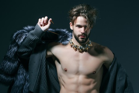 Man with fur coat on grey background. Cinderella prince with crown and muscular torso, chest. Freak, gay and transvestite. Drag queen, homosexual and trans. Winter fashion, jewelry, accessory. Stock Photo