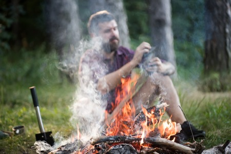 Flame and smoke from bonfire with blurred man sharpen axe on natural background. Summer camping, hiking, vacation concept.