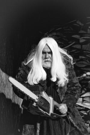 Oude mensendruïde met lang zilveren haar en baard in bontjas die grote kettingzaag zonnige dag openlucht houden Stockfoto