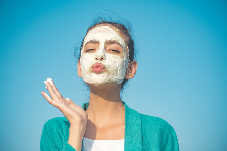 Woman send air kiss with cosmetic mask on face on blue sky. Beauty, nature, youth, skin care, rejuvenation concept 免版税图像
