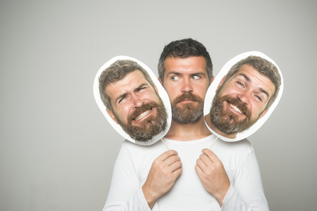 Hipster with serious, happy and scary face hold portrait nameplate. Barber fashion and beauty. Feeling and emotions. Guy or bearded man on grey background. Man with long beard and mustache. Banco de Imagens