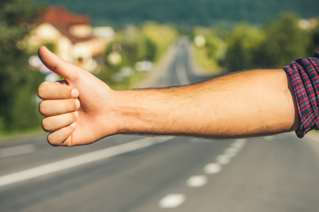 Hitchhiker sign on road. Thumb up male hand gesture outdoors. Hitchhiking, hitching, thumbing, auto stop concept. Travel, trip, vacation, wanderlust.