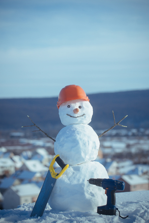 Building and repair work. Happy holiday and celebration. Snowman builder in winter in helmet. Christmas or xmas decoration. New year snowman from snow with saw and screwdriver. Stock Photo