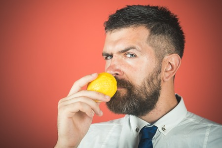 Man with long beard smell lemon. Vegetarian, health and wellbeing. Vitamin citrus at hipster on red background. Fruit and healthy organic food. Dieting and fitness, copy space