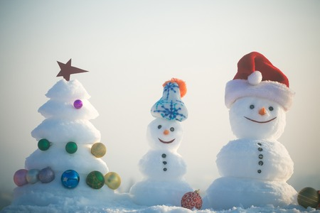 celebration smiley: Snowmen with smiley faces in hats on winter day. xmas tree decorated with star and balls. Merry Christmas and happy new year. Holidays celebration concept. Snow sculptures on white sky background.