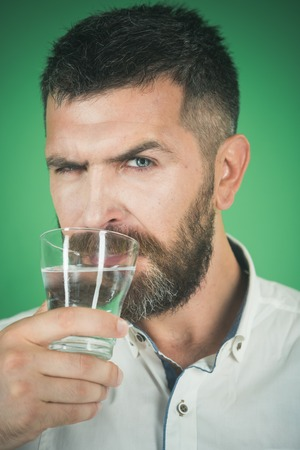 serious hipster drink clean healthy water, refreshing. Man with long beard hold water glass on green background. Health and dieting. Hangover and thirst. Life source and healthcare.