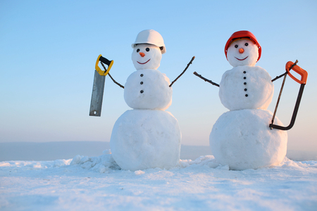 Christmas or xmas decoration. New year snowman from snow with saw. Building and repair work. Happy holiday and celebration. Snowman builder in winter in helmet. Archivio Fotografico