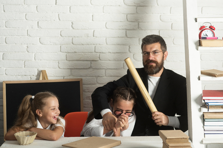 Teacher and schoolgirls on classroom background. Girls and bearded man sit at desk and have fun. Kid, older sister and their tutor with cheerful and proud faces. Home schooling concept