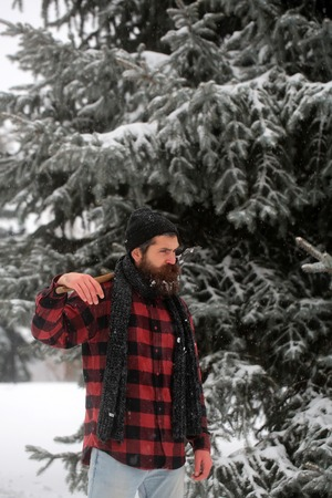 Christmas hipster lumberjack with ax in wood.. Man with beard in winter forest with snow hold axe. Wanderlust, hiking and travel. New year man in snowy cold forest. Winter holiday and celebration.