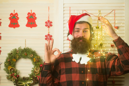 Christmas man with beard on happy face and garland. santa claus man at decoration with garland. Party and celebration. Winter holiday and xmas. New year guy with illuminated wire and toy, ok gesture Stock Photo
