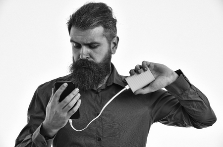 bearded man, long beard, brutal caucasian hipster with moustache charging mobile or cell phone with green power bank battery, has serious face, in brown color shirt isolated on white background