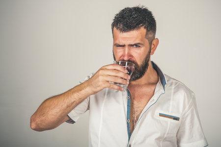 Man with long beard hold water glass on grey background. Hipster drink clean healthy water, refreshing. Health and dieting. Hangover and thirst. Life source and healthcare. Imagens