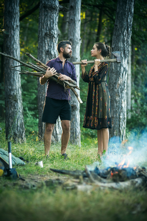 Woman lumberjack hold axe. Man with bunch of firewood. Couple of hikers make bonfire in forest. Camping, hiking, lifestyle. Summer vacation concept. Stock Photo