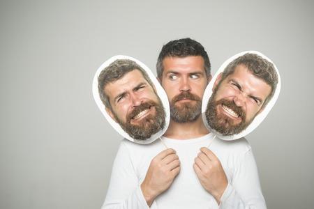 Kapper mode en schoonheid. Hipster met ernstig en boos gezicht houdt portret naamplaatje. Gevoel en emoties. Man of bebaarde man op grijze achtergrond. Man met lange baard en snor.