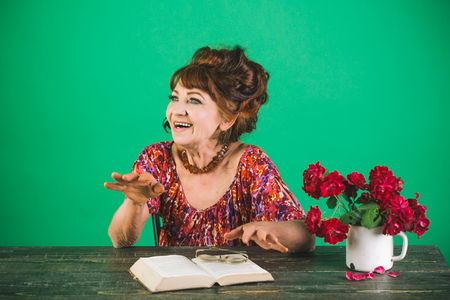 Teacher or professor, education, teachers day. happy old lady or grandmother. Pension and retirement, old age. Old woman reading book with glasses at flowers. Writer and poet, granny read fairytale.