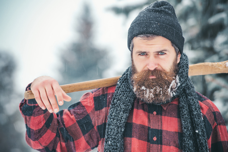 New year man in snowy cold forest. Man with beard in winter forest with snow hold axe. Wanderlust, hiking and travel. Christmas hipster lumberjack with ax in wood.. Winter holiday and celebration. Stock Photo