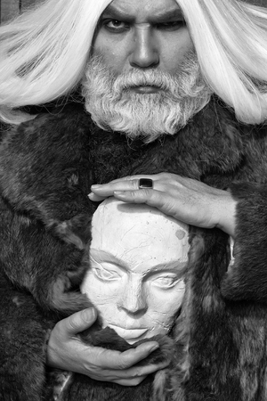old druid bearded man with long beard on serious face and hair in fur coat holding white sculpture head in hands with ring Stock Photo