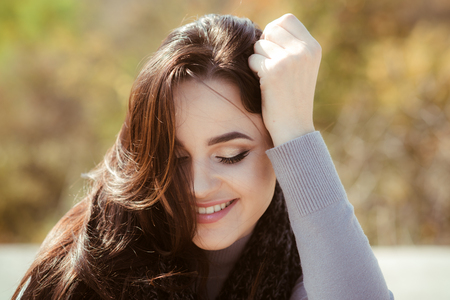 Skincare, youth, health concept. Girl face with makeup on healthy skin in nature. Dental care, stomatology. Woman happy smile with long brunette hair on sunny day. Fashion, beauty, visage.