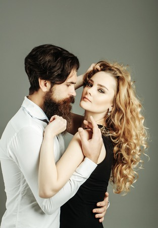 Woman and man haircut. Couple in love with trendy hairstyle hug on grey background. Barber or hairdressing salon. Girl with long blond hair and hipster with beard, mustache. Beauty, fashion concept.