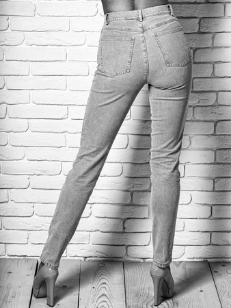 long beautiful female legs in slim stylish denim jeans or pants blue color and fashionable shoes on heels of young cute woman or girl with sexy buttocks on wooden floor and white brick wall background