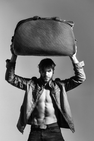 handsome muscular man or bearded macho guy with naked torso and sexy body holds big bag or suitcase in fashionable brown leather jacket and pants on grey background