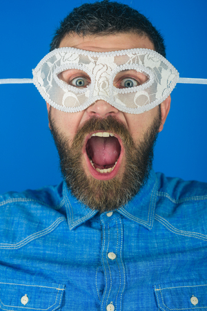 mask on man with beard on shouting face blue background, homosexual and fetish, gay and lgbt, holiday party and carnival Stock Photo