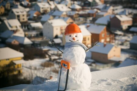 Christmas or xmas decoration. Snowman builder in winter in helmet. Building and repair work. Happy holiday and celebration. New year snowman from snow with saw.