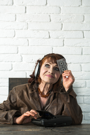 Granny dj in headset with cassette player. Old school music player, radio. Old woman with cassette recorder listen music in headphones. Spy and operator. Audio book and new technology, education.