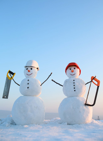 New year snowman from snow with saw. Happy holiday and celebration. Building and repair work. Snowman builder in winter in helmet. Christmas or xmas decoration. Stock Photo