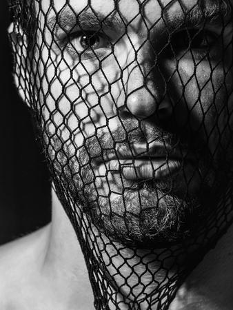 若い男のひげと金髪ひげを生やした男性または強盗強盗ギャングは、暗い背景に顔が黒タイツ ストッキングのマスクを着ています。