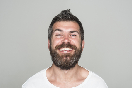 Hipster with happy face. Man with long beard and mustache. Feeling and emotions. Guy or bearded man on grey background. Barber fashion and beauty. 版權商用圖片