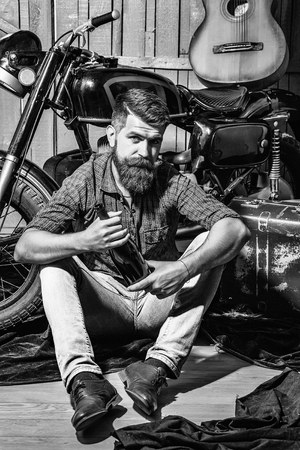 Bearded man hipster biker brutal male with beard and moustache sits with bottle near motorcycle on wooden background