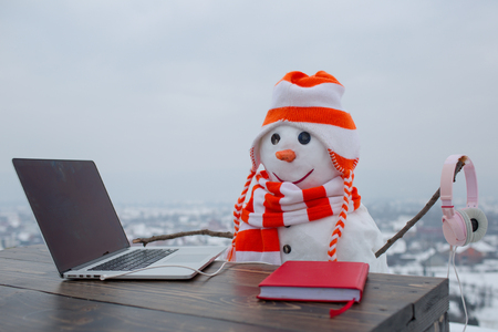 New year snowman in hat. Happy holiday celebration, new technology. Christmas and education, fairytale. Snowman in winter with laptop, headset and book. Xmas or christmas decoration, audio book.