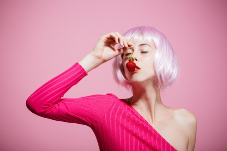 Girl in artificial hair hold red berry in mouth. Fruit and vitamin. Skincare, spa and health. Beauty and fashion. Woman in wig has no makeup on pink background