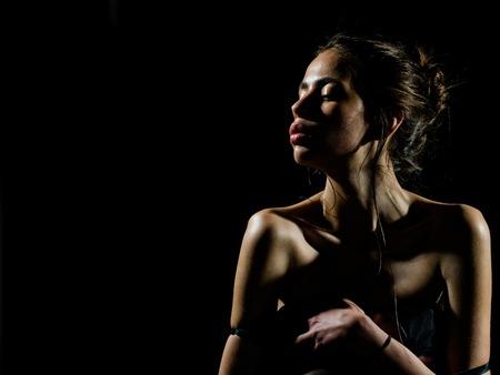 スキンケア、うるおい、ウェルネス。黒い背景に油性または濡れ肌を持つ女の子。美しさ、ファッション、見て。官能的な顔と裸の肩を持つ女性。