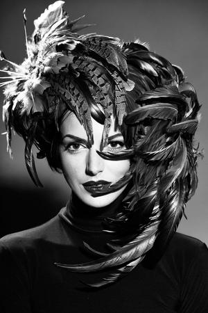 ハロウィーンやカーニバルの休日の衣装、クローズアップとして美しい羽の帽子茶色の色でかわいい顔に赤い唇を持つ若いセクシーな女性や女の子