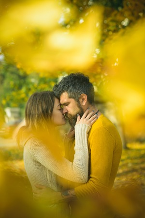 Love relationship and romance. Couple in love in autumn park. Autumn happy couple of girl and man outdoor. Man and woman at yellow tree leaves. Nature season and fall holiday.