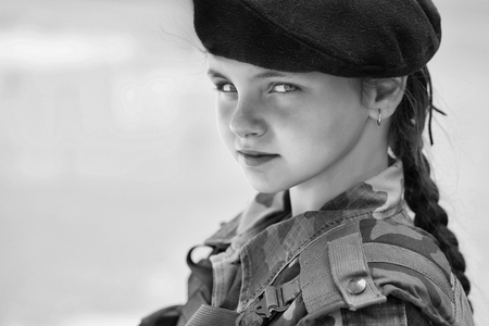 Young girl child with pretty serious face brunette in army ammunition black beret on blue background outdoor