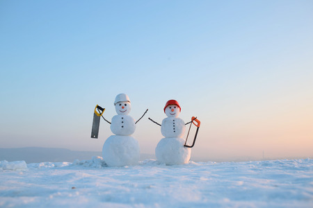 Snowman builder in winter in helmet. New year snowman from snow with saw. Building and repair work. Happy holiday and celebration. Christmas or xmas decoration.