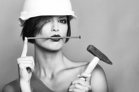 Attractive girl with dark short hair, red lips, blue dress in white hard hat with hummer and nail in the mouth on the grey background