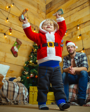Christmas happy child and father with gift on wooden background. Xmas party celebration, fathers day. New year small boy son and man. Winter holiday. Santa claus kid and bearded man at Christmas tree.