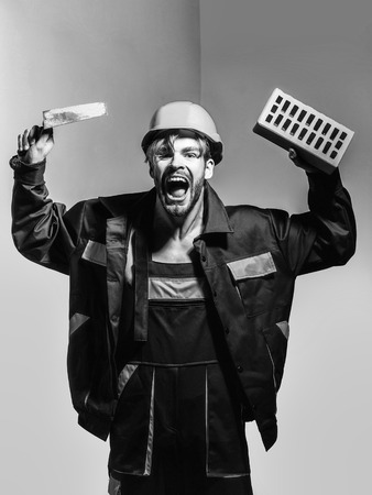 Excited man shouting handsome builder construction mason worker bricklayer in orange hard hat and boilersuit keeps brick and trowel on grey background
