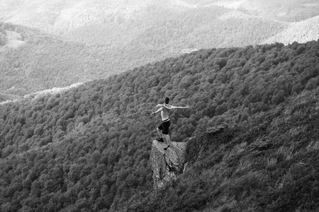 handsome man or guy with raised hands in shorts with blanket and naked torso stands on slope in summer on mountains covered with forest, black and white