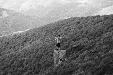 knappe man of man met opgeheven handen in korte broek met deken en naakte torso staat op helling in de zomer op bergen bedekt met bos, zwart en wit