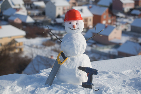 Building and repair work. Happy holiday and celebration. New year snowman from snow with saw and screwdriver. Snowman builder in winter in helmet. Christmas or xmas decoration. Stock Photo