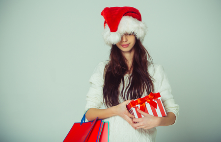 New year girl with present shopping bag, black friday. Xmas party and holiday celebration. Santa claus girl with gift. Boxing day and christmas sale. Christmas woman with happy face.