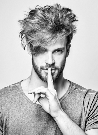 Handsome man or fashion model, bearded hipster with beard and stylish, shaggy, blond hair, hairstyle, makes hush, silence, gesture, finger on lips on grey background Reklamní fotografie