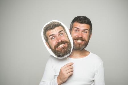 man met lange baard op blij gezicht met papieren naamplaatje op grijze achtergrond Stockfoto