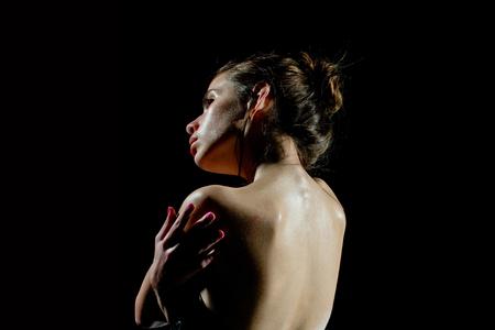 官能的な顔と裸の背中を持つ女性。黒い背景にオイリー肌を持つ少女。スキンケア、水分、ウェルネス。美容、ファッション、見てください。純度